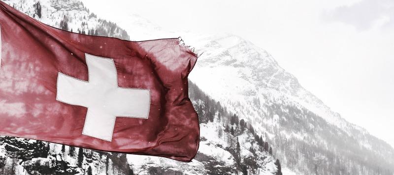 Drapeau suisse accroché à un mât qui se trouve lui même sur la façade d'un immeuble ancien
