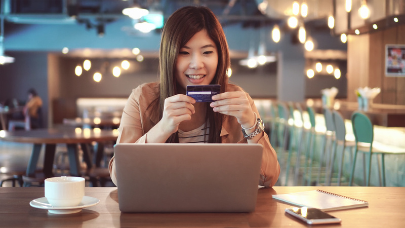 Asian businesswoman in casual suit using the credit card with computer for online shopping at co-working space, business technology and lifestyle concept