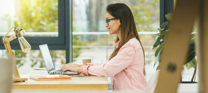 Portrait of a businesswoman sitting on her workplace in the office, typing, looking at pc screen