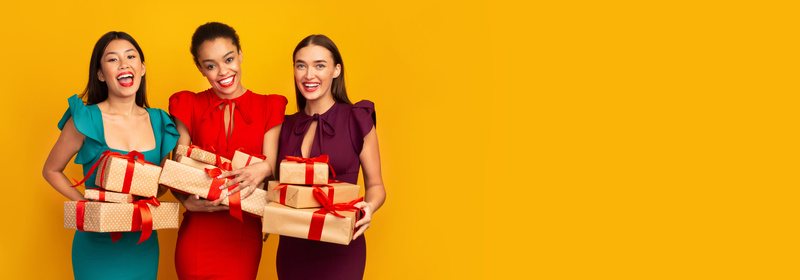 Three Multiethnic Women Holding Wrapped Gifts Boxes Smiling, Panorama