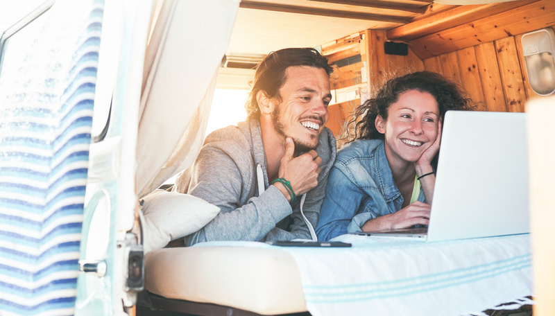 Happy couple watching videos on their computer inside minivan at sunset - Travel couple using laptop during their journey on a vintage mini van with wood interior