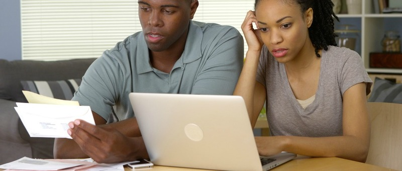Frustrated young Black couple going over bills and finances online