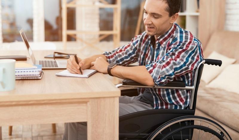 Homme en fauteuil roulant, attablé