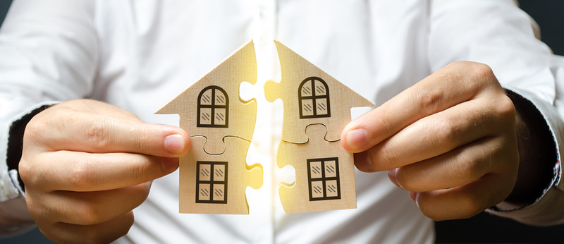 A man connects two puzzles into a whole house above the inscription Mortgage. Construction of your own residential building. Buying a home on credit loan, improvement of living conditions