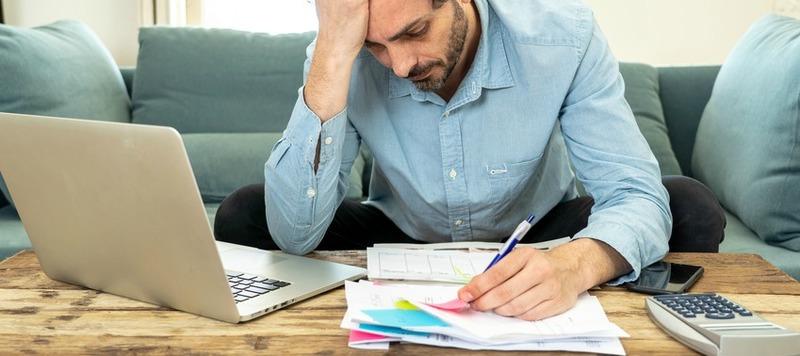 jeune homme stressé dettes étalées table