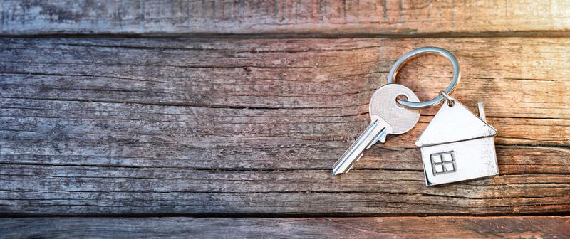 porte clé avec petite maison sur fond boisé