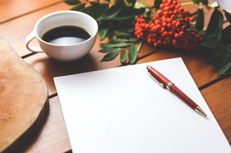 page blanche avec stylo sur table en bois