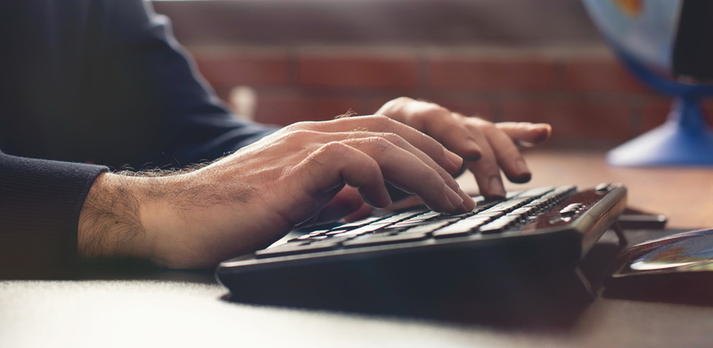 Male Hands Working On Computer Keyboard On Working Table In Office