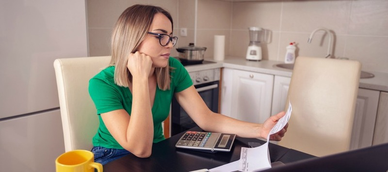 Single woman at home planning family budget and finances..