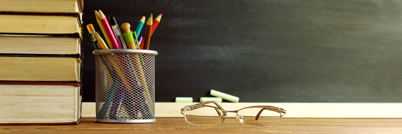 Glasses teacher books and a stand with pencils on the table, on the background of a blackboard with chalk. The concept of the teacher's day. Copy space
