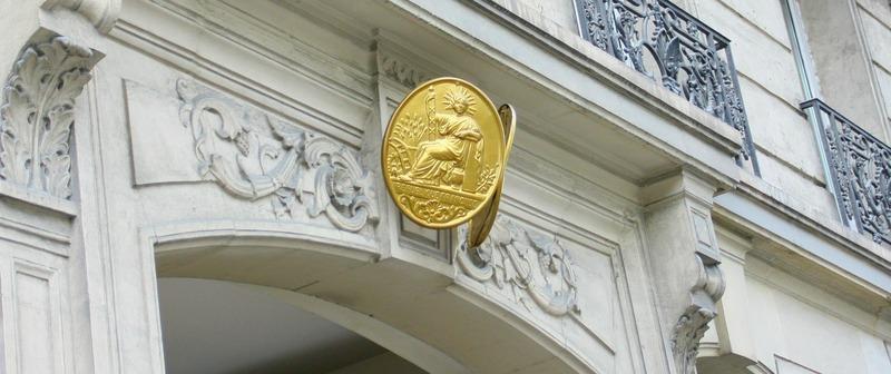 plaque de notaire jaune sur bâtiment citadin