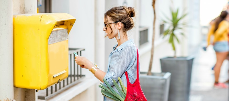 Young woman putting letter to the old yellow mailbox standing with mesh bag full of food outdoors on the street