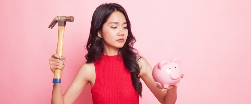 Asian woman with pig coin bank and hammer.