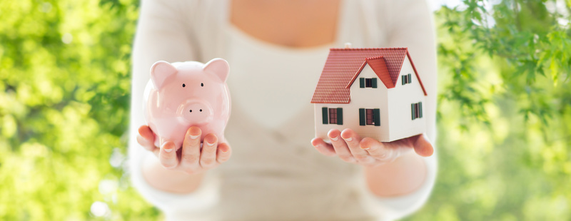 mortgage, investment, real estate and property concept - close up of woman holding home or house model and piggy bank over green natural background
