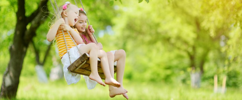 Two cute little sisters having fun on a swing together in beautiful summer garden on warm and sunny day outdoors