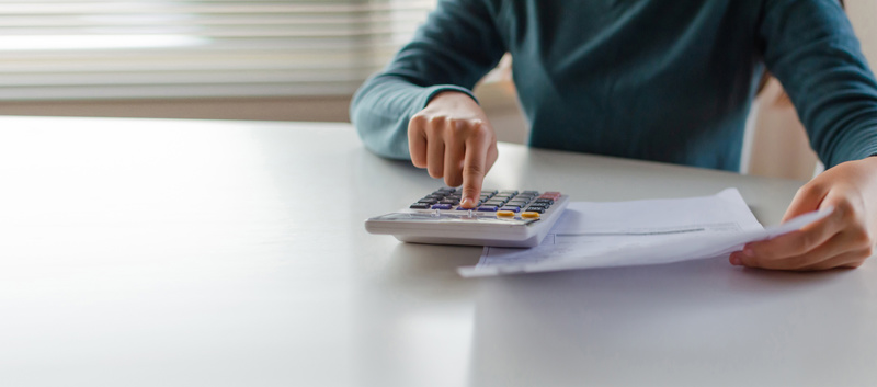 panoramic banner. hand of young woman using calculator for calculating family budget cost bills on desk in home office, plan money cost saving, investment, business finance, expenses, income .