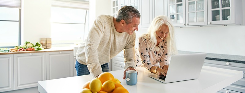 Senior couple relaxing in a kitchen with a laptop