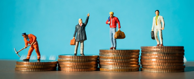 Miniature people, group of businessman standing on stack coins using as business and financial concept