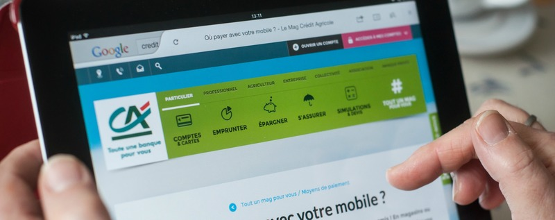 closeup of woman hands on the credit agricole home page of web site on tablet