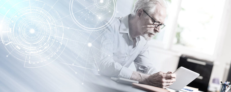 Senior businessman using a digital tablet; light effect