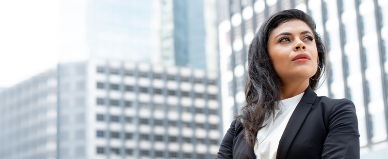 Powerful Latin businesswoman in city office building banner background