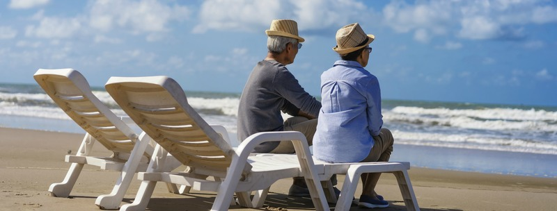 Senior couple sitting on chairs on the beach and looking at the ocean in a romantic,Elderly life insurance,Men take care of each other when aging.