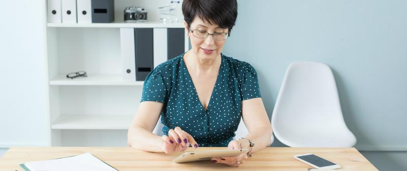 Business, technology and people concept - middle aged woman using a gadget in office