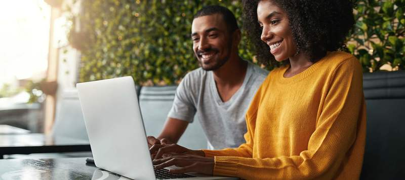 Happy young couple in café looking at laptop