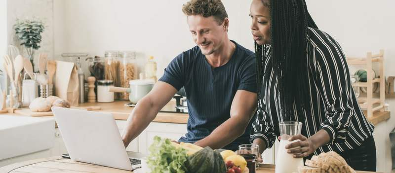 Multi-ethnic couple having a breakfast while working at home