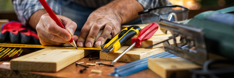 Adult carpenter craftsman with a pencil and the carpenter's square trace the cutting line on a wooden table. Construction industry, housework do it yourself. Stock photography