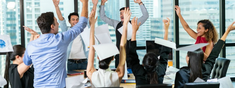 Multiethnic diverse Group of business people celebrating by throwing papers in the air and having fun in office.Happy business people cheering together,celebrate project success