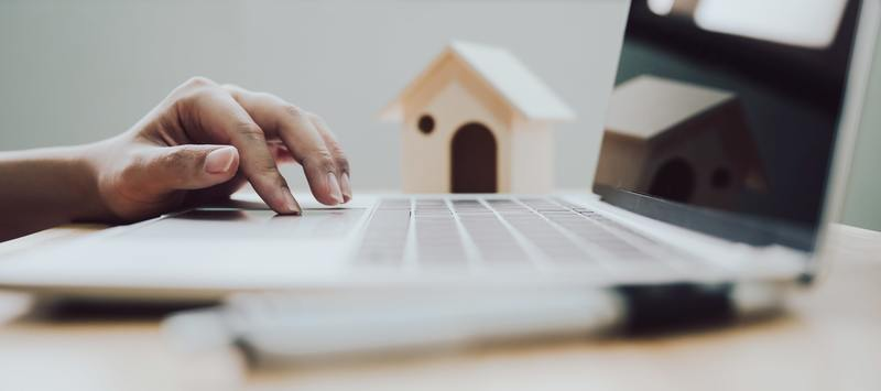 Concept of property investment, Mortgage and real estate residental house. Hand using laptop with pen and wooden house