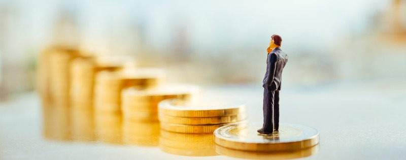 Miniature people: small figure businessman standing on a stack of coins with city background. Money, Financial, Business Growth concept.