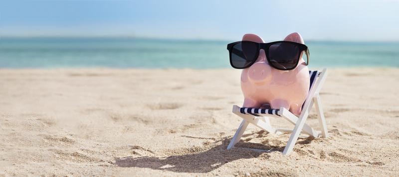 Pink Piggybank On Deck Chair Over The Sandy Beach