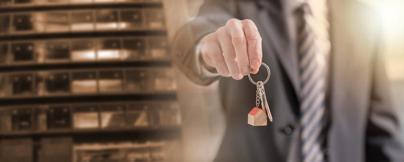 Estate agent offering house keys; multiple exposure