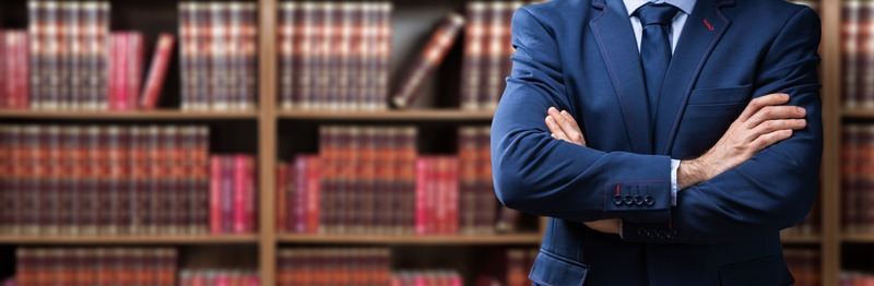 Midsection Of Lawyer Standing Against Bookshelf