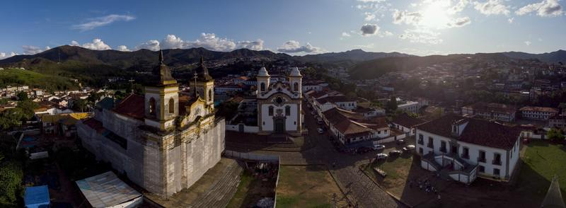 Aerial 360 degrees panorama of the central historical square with two churches in the colonial mining city of Mariana in Minas Gerais, Brazil, with one under renovation against a blue sky with clouds