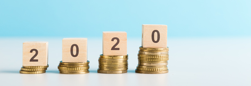 2020 New year saving money and financial planning concept. Stack of coins w/ number 2020 on wood table over green background. Creative idea for business growth, investment, profit and banking.