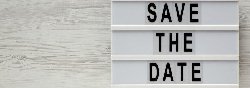 'Save the date' words on a modern board on a white wooden background, top view. Overhead, from above, flat lay. Space for text.