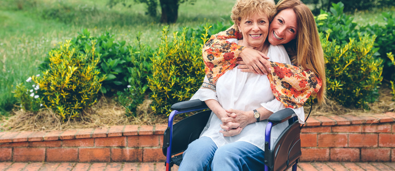 Daughter embracng her senior mother in wheelchair in the garden