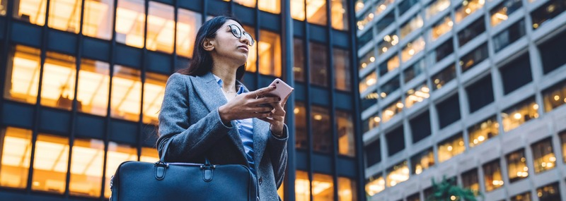 Young female with smartphone standing by skyscraper