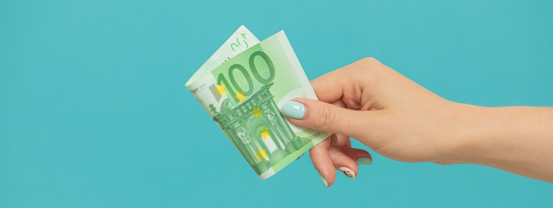 Female hands holding euro banknotes on a blue background.