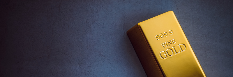 An ingot of gold metal bullion of pure brilliant diagonally located on a blue textured background.