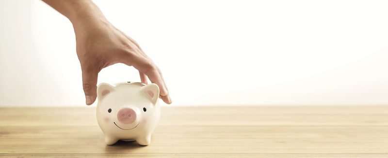 Man hand holding piggy bank on wood table.A saving money for future investment concept.