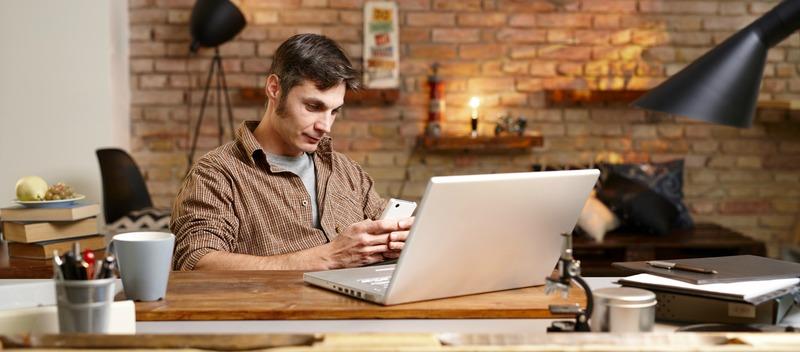 Casual man using mobilephone, sitting at desk, having laptop, texting.
