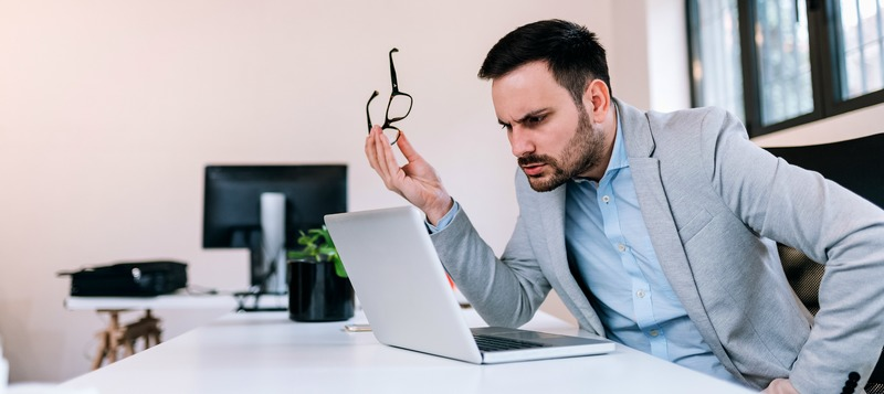 Close-up image of a serious business man holding eyeglasess while looking at laptop screen.