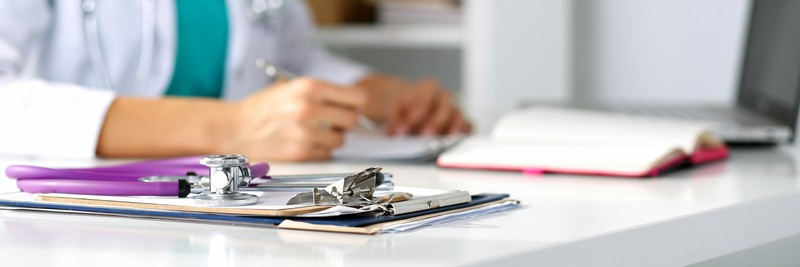 Stethoscope head lying on medical forms on clipboards closeup