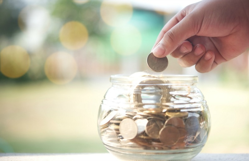 Hand drop money coins to jar. Concept of Insurance money savings for retirement planning .